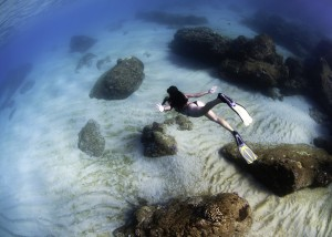 Girl diving in Waimea Bay Maui